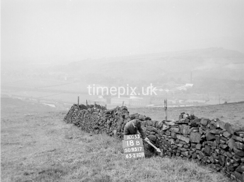 SD951718B, Man marking Ordnance Survey minor control revision point with an arrow in 1950s