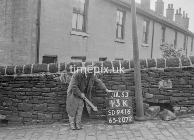 SD941613K, Man marking Ordnance Survey minor control revision point with an arrow in 1950s