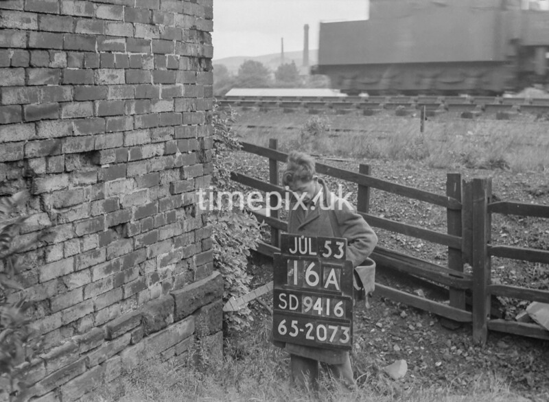 SD941616A, Man marking Ordnance Survey minor control revision point with an arrow in 1950s