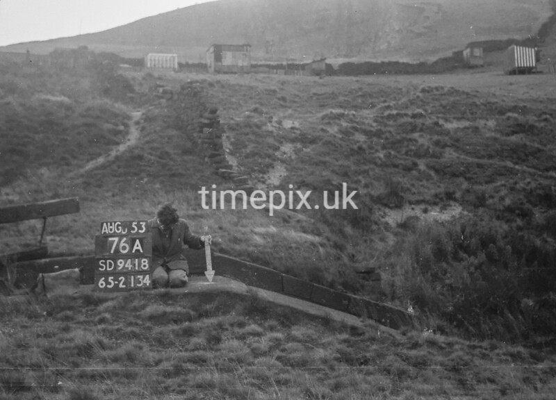 SD941876A, Man marking Ordnance Survey minor control revision point with an arrow in 1950s