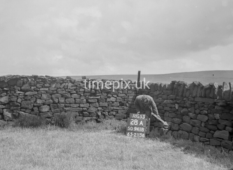 SD941828A, Man marking Ordnance Survey minor control revision point with an arrow in 1950s
