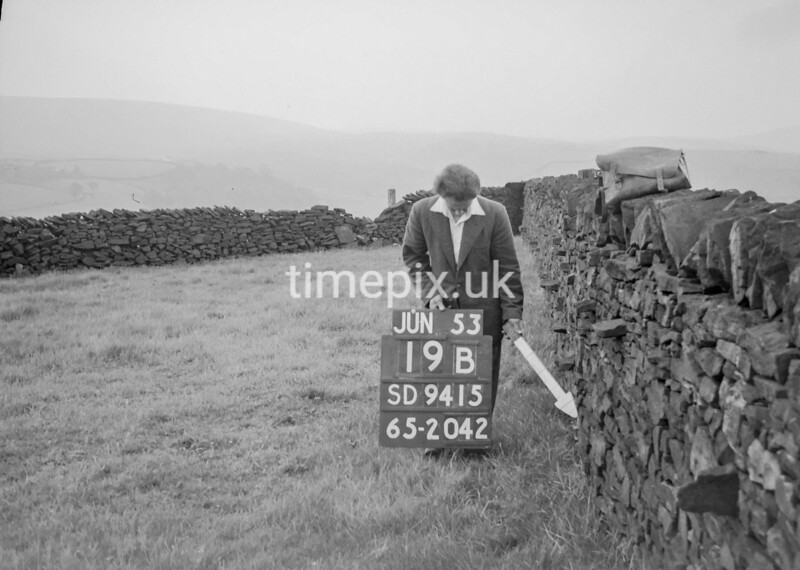 SD941519B, Man marking Ordnance Survey minor control revision point with an arrow in 1950s