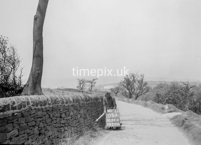 SD941405A, Man marking Ordnance Survey minor control revision point with an arrow in 1950s