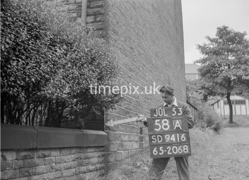 SD941658A, Man marking Ordnance Survey minor control revision point with an arrow in 1950s