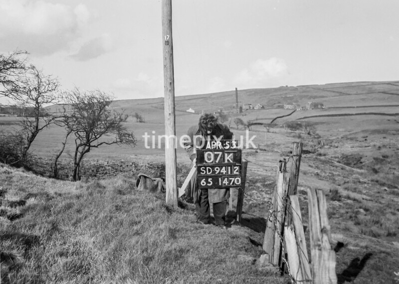 SD941207K, Man marking Ordnance Survey minor control revision point with an arrow in 1950s