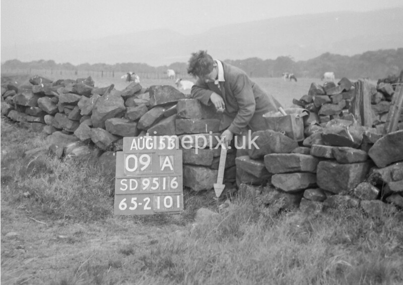SD951609A, Man marking Ordnance Survey minor control revision point with an arrow in 1950s
