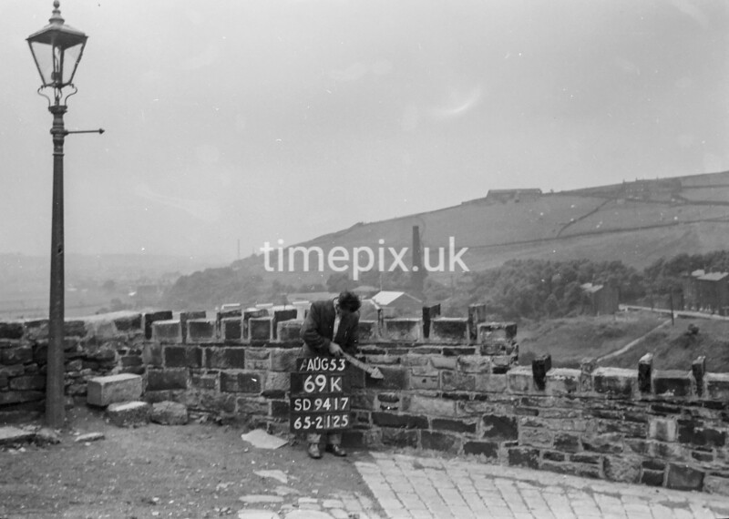 SD941769K, Man marking Ordnance Survey minor control revision point with an arrow in 1950s