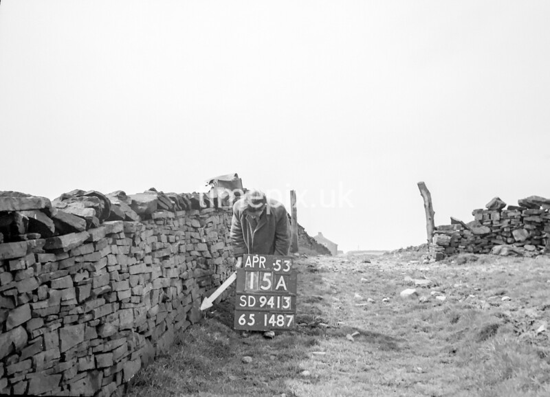 SD941315A, Man marking Ordnance Survey minor control revision point with an arrow in 1950s