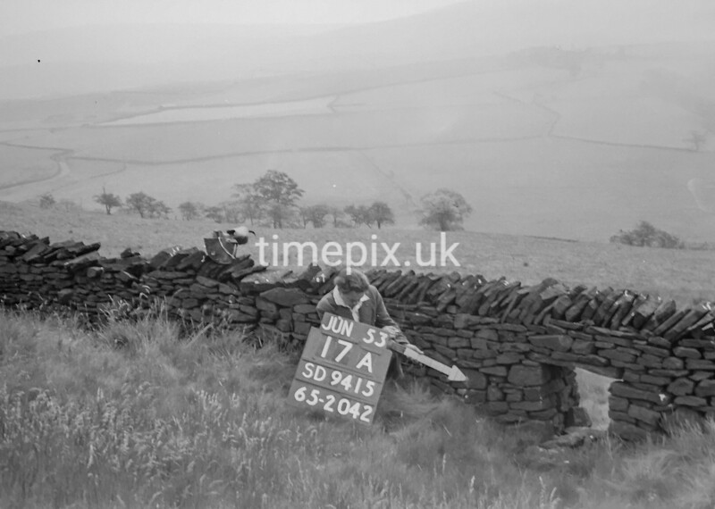 SD941517A, Man marking Ordnance Survey minor control revision point with an arrow in 1950s
