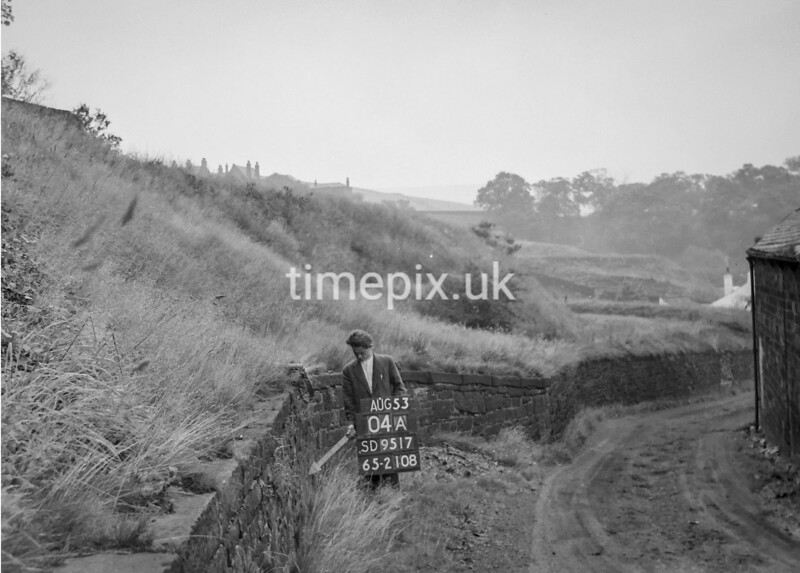 SD951704A, Man marking Ordnance Survey minor control revision point with an arrow in 1950s