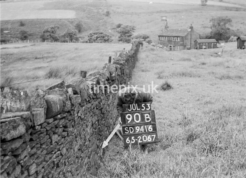 SD941690B, Man marking Ordnance Survey minor control revision point with an arrow in 1950s