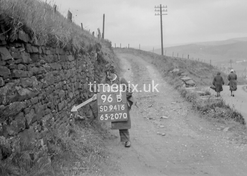SD941696B, Man marking Ordnance Survey minor control revision point with an arrow in 1950s