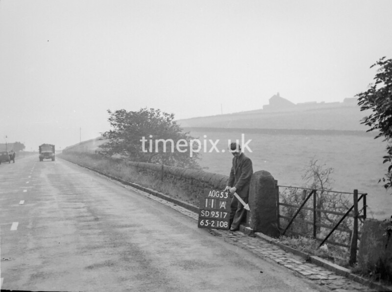 SD951711A, Man marking Ordnance Survey minor control revision point with an arrow in 1950s