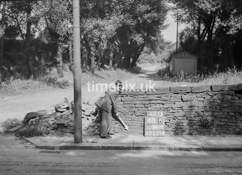 SD941748B, Man marking Ordnance Survey minor control revision point with an arrow in 1950s