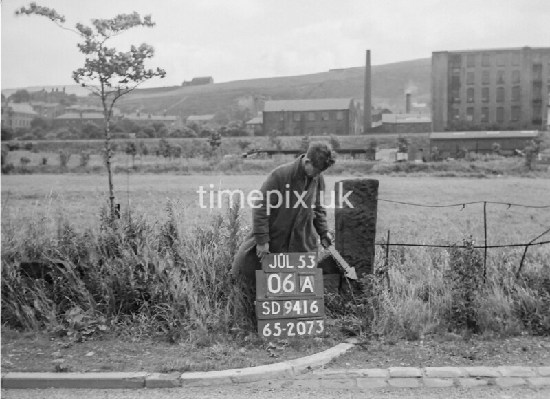 SD941606A, Man marking Ordnance Survey minor control revision point with an arrow in 1950s