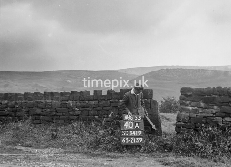SD941940A, Man marking Ordnance Survey minor control revision point with an arrow in 1950s