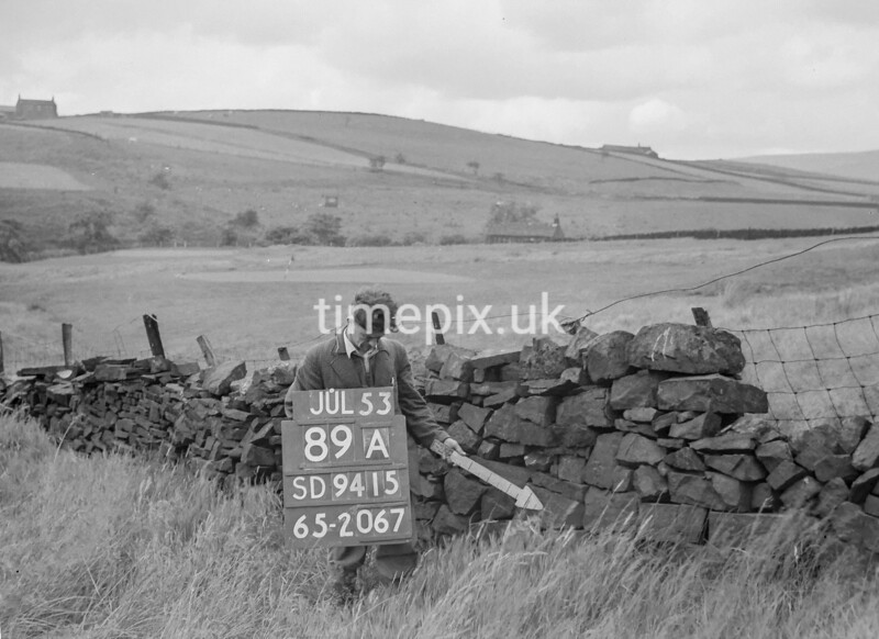 SD941589A, Man marking Ordnance Survey minor control revision point with an arrow in 1950s