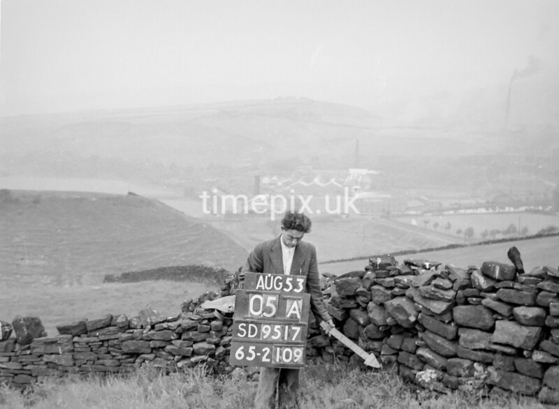 SD951705A, Man marking Ordnance Survey minor control revision point with an arrow in 1950s