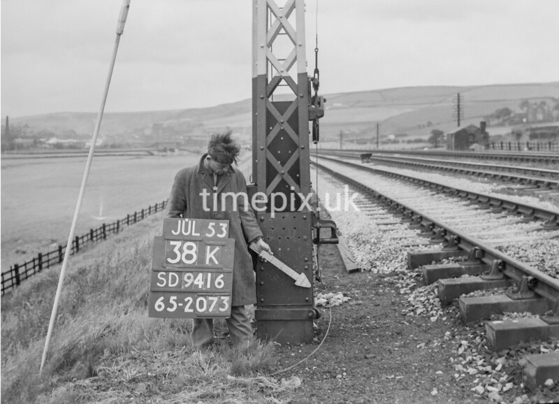 SD941638K, Man marking Ordnance Survey minor control revision point with an arrow in 1950s