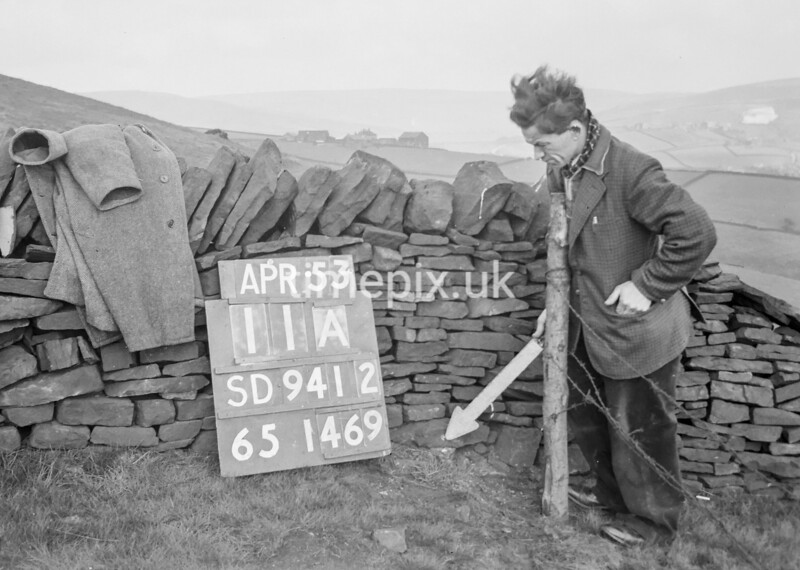 SD941211A, Man marking Ordnance Survey minor control revision point with an arrow in 1950s