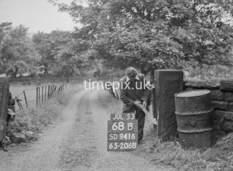 SD941668B, Man marking Ordnance Survey minor control revision point with an arrow in 1950s