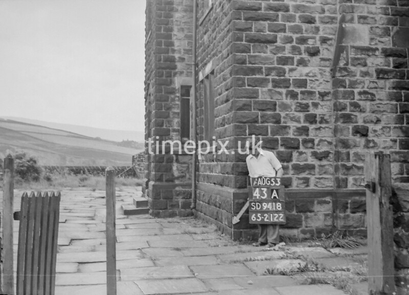 SD941843A, Man marking Ordnance Survey minor control revision point with an arrow in 1950s