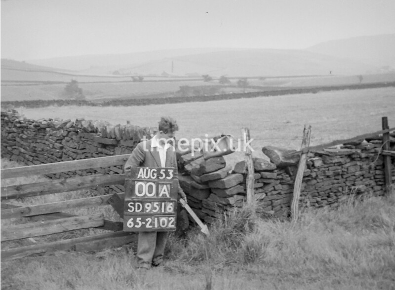 SD951600A, Man marking Ordnance Survey minor control revision point with an arrow in 1950s
