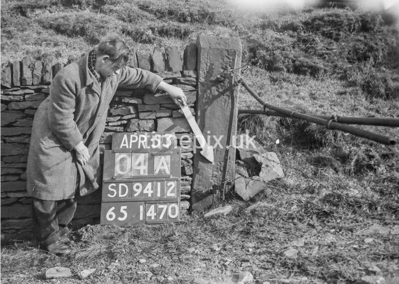 SD941204A, Man marking Ordnance Survey minor control revision point with an arrow in 1950s