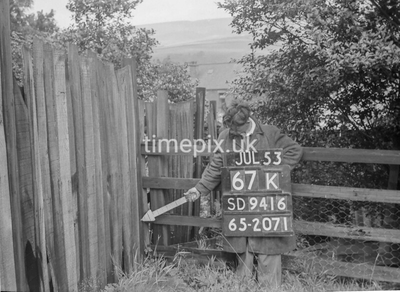 SD941667K, Man marking Ordnance Survey minor control revision point with an arrow in 1950s