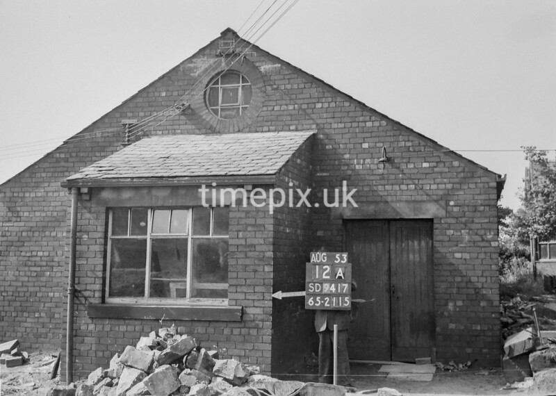 SD941712A, Man marking Ordnance Survey minor control revision point with an arrow in 1950s