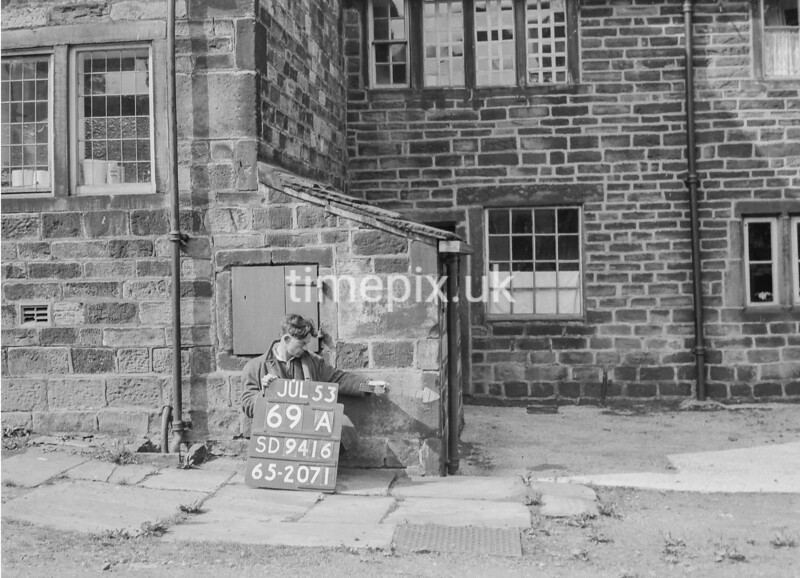 SD941669A, Man marking Ordnance Survey minor control revision point with an arrow in 1950s