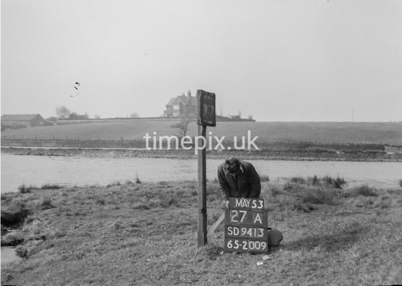 SD941327A, Man marking Ordnance Survey minor control revision point with an arrow in 1950s