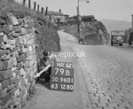 SD960179B, Man marking Ordnance Survey minor control revision point with an arrow in 1950s