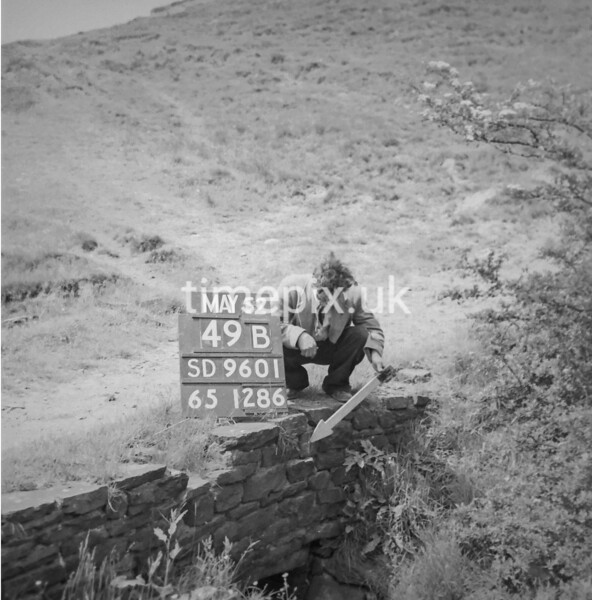 SD960149B, Man marking Ordnance Survey minor control revision point with an arrow in 1950s
