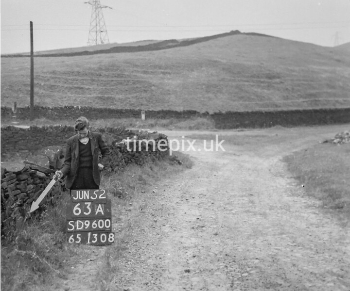 SD960063A, Man marking Ordnance Survey minor control revision point with an arrow in 1950s