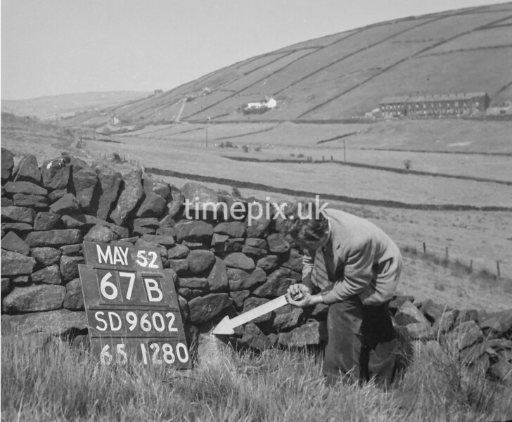 SD960267B, Man marking Ordnance Survey minor control revision point with an arrow in 1950s