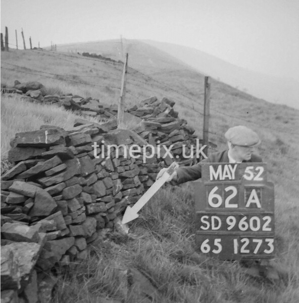 SD960262A, Man marking Ordnance Survey minor control revision point with an arrow in 1950s