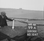 SD950299A, Man marking Ordnance Survey minor control revision point with an arrow in 1950s