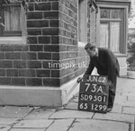 SD950173A, Man marking Ordnance Survey minor control revision point with an arrow in 1950s