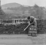 SD970143A, Man marking Ordnance Survey minor control revision point with an arrow in 1950s