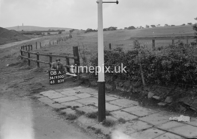 SD950008A, Man marking Ordnance Survey minor control revision point with an arrow in 1950s