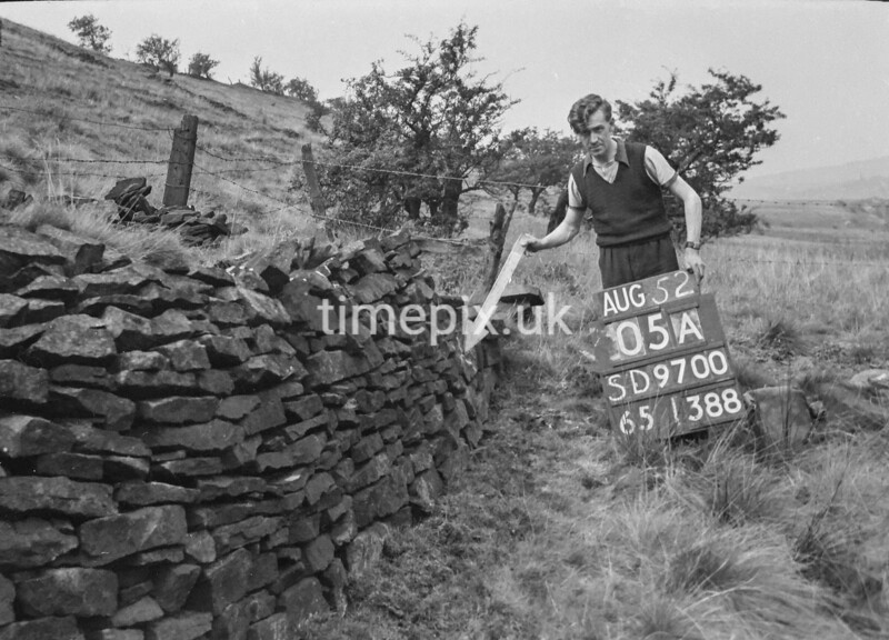 SD970005A, Man marking Ordnance Survey minor control revision point with an arrow in 1950s