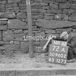 SD960272B, Man marking Ordnance Survey minor control revision point with an arrow in 1950s