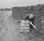 SD950285A, Man marking Ordnance Survey minor control revision point with an arrow in 1950s