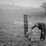 SD960230B, Man marking Ordnance Survey minor control revision point with an arrow in 1950s
