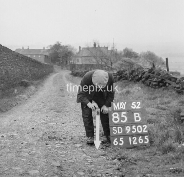 SD950285B, Man marking Ordnance Survey minor control revision point with an arrow in 1950s