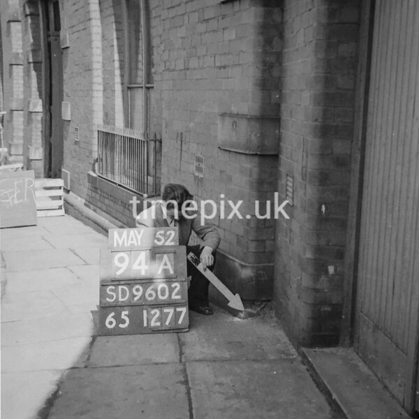SD960294A, Man marking Ordnance Survey minor control revision point with an arrow in 1950s
