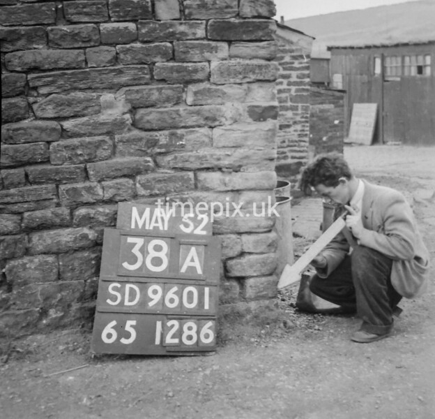 SD960138A, Man marking Ordnance Survey minor control revision point with an arrow in 1950s