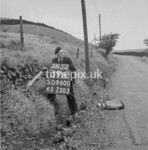 SD960059B, Man marking Ordnance Survey minor control revision point with an arrow in 1950s
