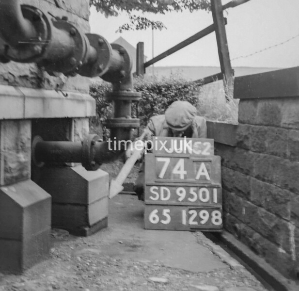SD950174A, Man marking Ordnance Survey minor control revision point with an arrow in 1950s